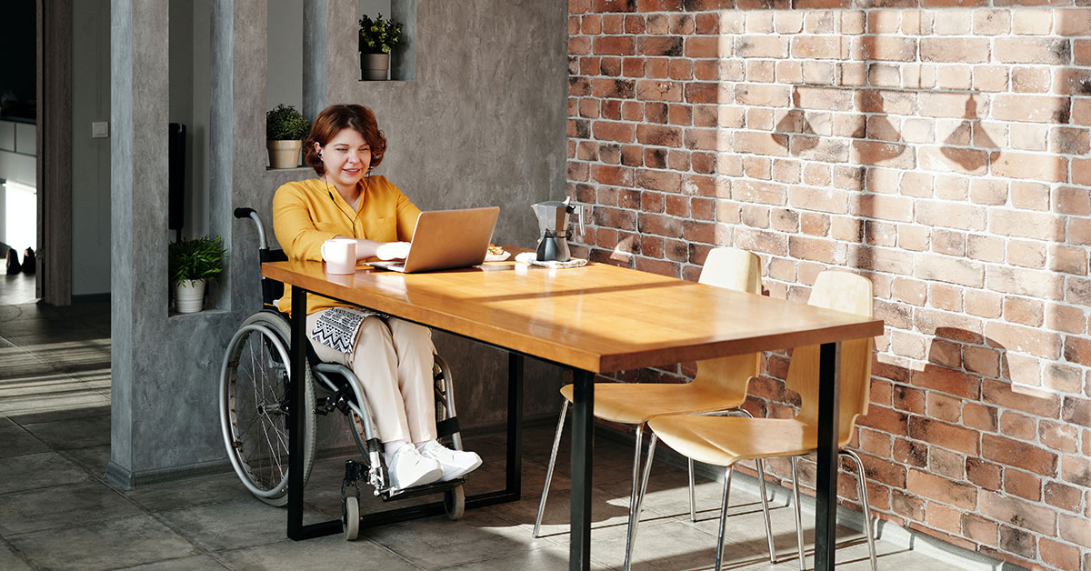 lady working on laptop from wheelchair